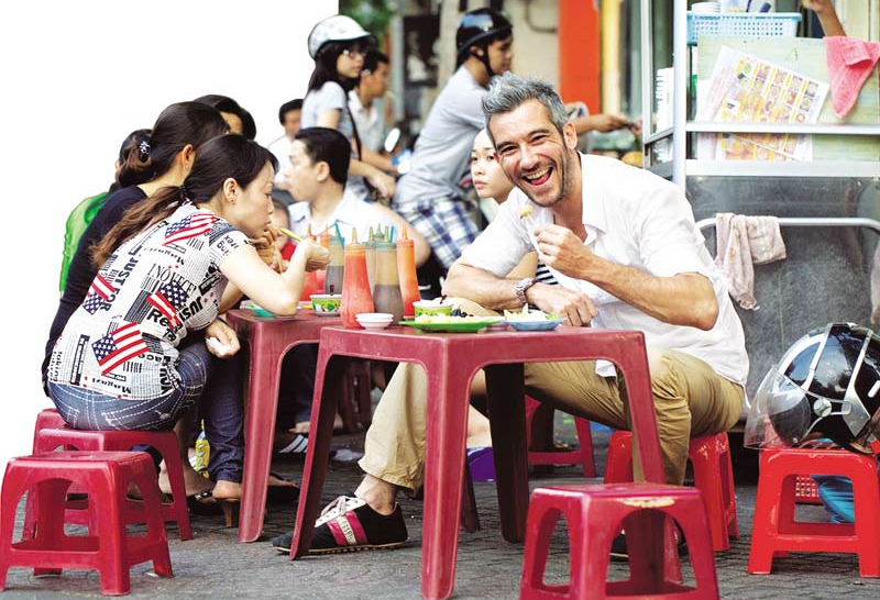Foreign travelers enjoy Saigon street foods